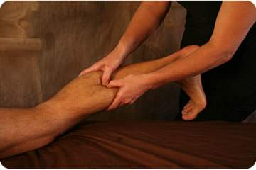 Therapist performing deep tissue massage on calf